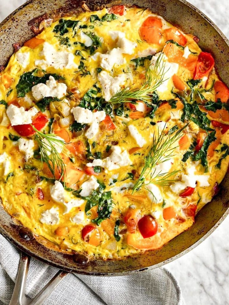 Birds eye view of the cooked frittata still in the skillet. Garnished with fronds of fresh dill.